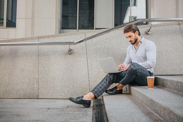 Rustige en vredige jongeman zit op trappen en werkt. hij kijkt naar het laptopscherm. er is een plastic kopje koffie op trappen. hij heeft het druk. Premium Foto