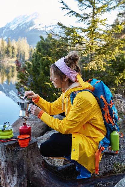 Rustige vrouwelijke reiziger zet koffie op het kooktoestel, poseert in de buurt van boomstronk, heeft pauze na omzwervingen Gratis Foto