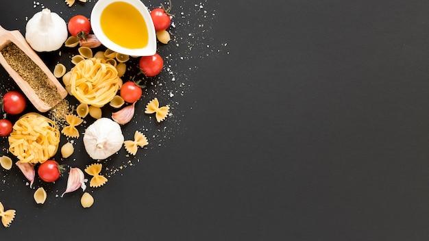 Ruw ingrediënt met tagliatelle; conchiclioni; tagliatelle; farfalle; olie op zwarte achtergrond Gratis Foto