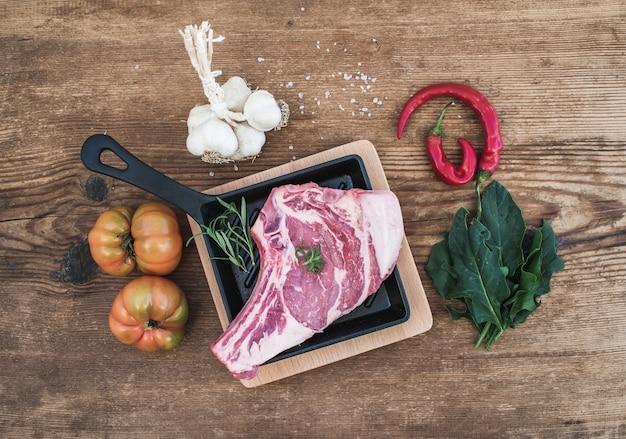 Ruw vers vleesribeye lapje vlees met peper, zout, spaanse peper, knoflook, spinazie, erfgoedtomaten en rozemarijn in het koken van pan over rustieke houten oppervlakte, hoogste mening. Premium Foto