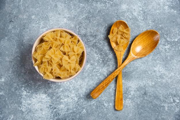 Ruwe bogen macaroni met een houten lepel op marmer. Gratis Foto