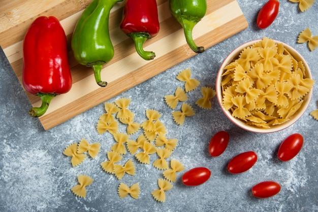 Ruwe bogen pasta met groenten op een houten bord. Gratis Foto