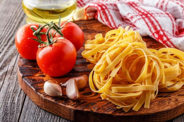 Ruwe deegwaren en tomaten op een scherpe raad Premium Foto