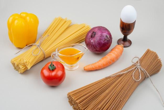 Ruwe deegwaren met groenten op witte achtergrond. hoge kwaliteit foto Gratis Foto