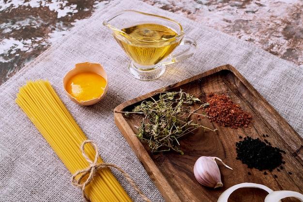 Ruwe droge spaghetti en gedroogde kruiden en eieren op bruin tafelkleed. Gratis Foto
