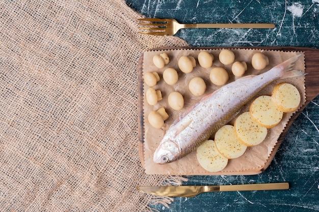 Ruwe hele vissen met olijven en gekookte aardappelschijfjes op een houten bord. Gratis Foto