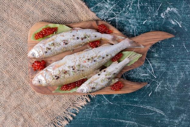 Ruwe hele vissen met rode kaviaar op een houten bord. Gratis Foto