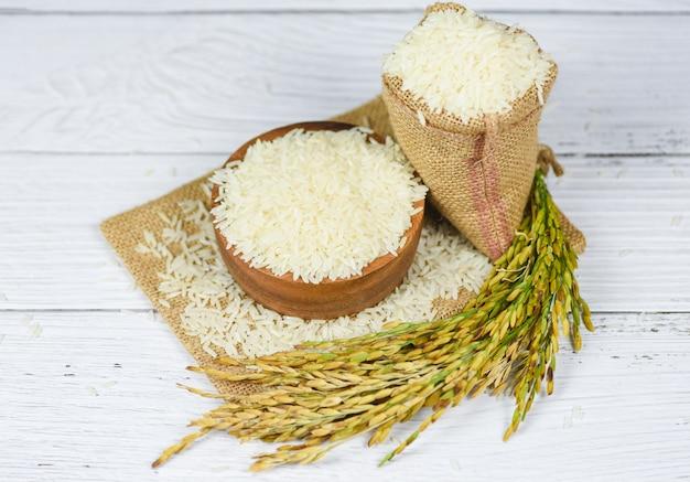 Ruwe jasmijnrijstkorrel met oor van padieveld landbouwproducten voor voedsel in aziatisch - thaise rijstwit op kom en de zak Premium Foto