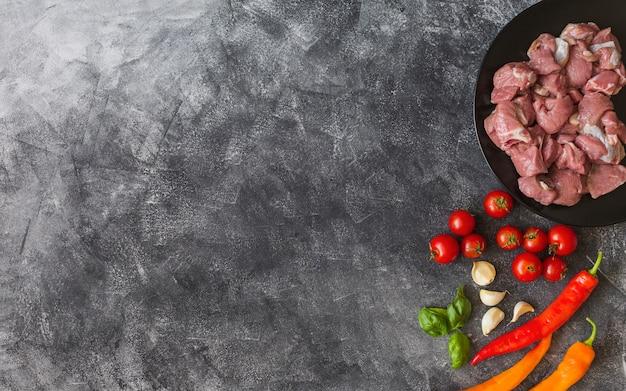 Ruwe kippen met ingrediënten op zwarte textuurachtergrond Gratis Foto