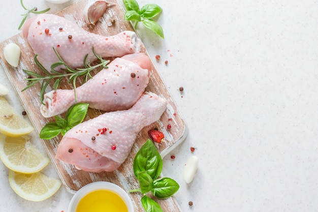 Ruwe kippentrommelstok op een snijplank met kruiden voorbereide fo Premium Foto