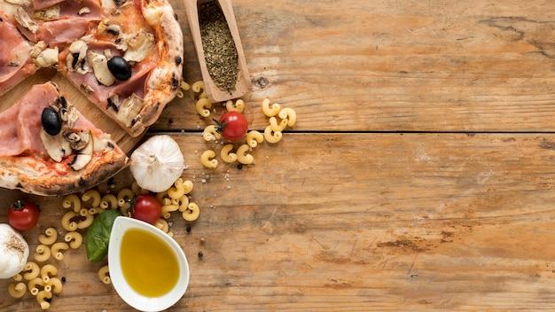 Ruwe macaroni voorbij; gebakken pizza en verse ingrediënten op houten plank Gratis Foto