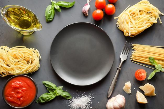 Ruwe pasta, spaghetti, tomaten, basilicum, parmezaan voor het bereiden van mediterrane gerechten. Premium Foto