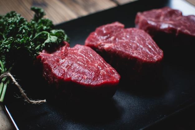 Ruwe rundvleeslapjes vlees op een zwarte plaat Gratis Foto