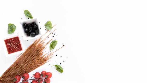 Ruwe spaghetti pasta en het is ingrediënten voor voorbereiding geïsoleerd op wit oppervlak Gratis Foto