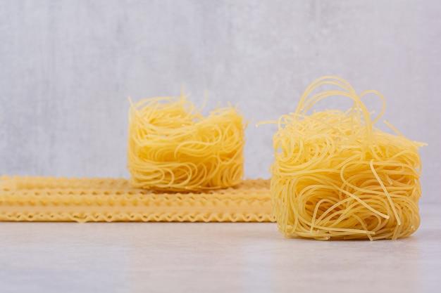 Ruwe spaghettinest en deegwaren op steenoppervlakte Gratis Foto