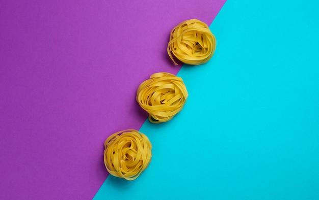 Ruwe tagliatelle pasta geïsoleerd op een blauw en paars Premium Foto