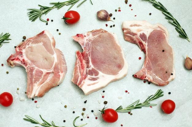 Ruwe varkensvleeslapje vlees op been op lichte oppervlakte Premium Foto