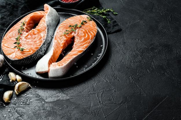 Ruwe zalmlapje vlees op een plaat met kruiden. atlantische vis. bovenaanzicht copyspace Premium Foto
