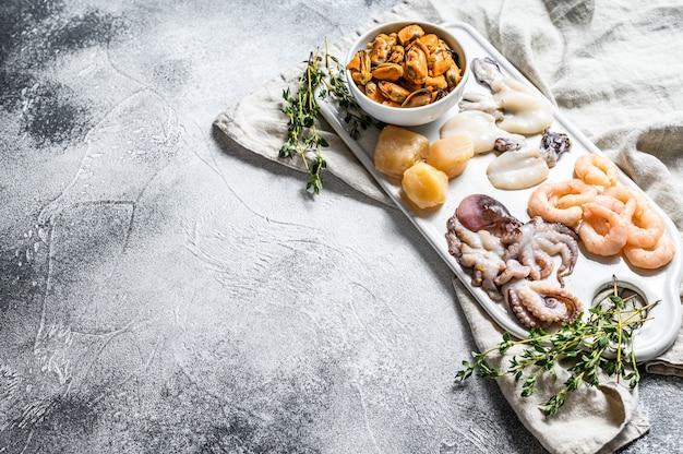 Ruwe zeevruchtenmengeling op een ceramische hakbordachtergrond Premium Foto
