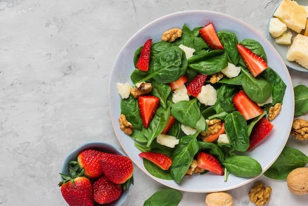 Salade met aardbei, spinaziebladeren, parmezaanse kaas en walnoten op betonnen tafel. gezond dieet voedsel Premium Foto