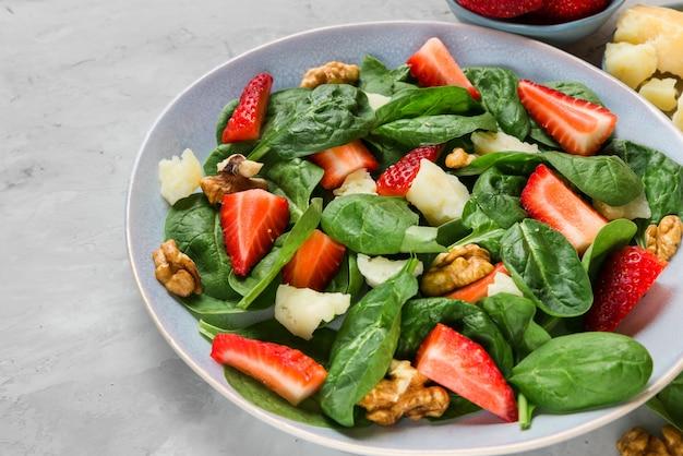 Salade met aardbeien, spinaziebladeren, parmezaanse kaas en walnoten. gezond dieet voedsel Premium Foto