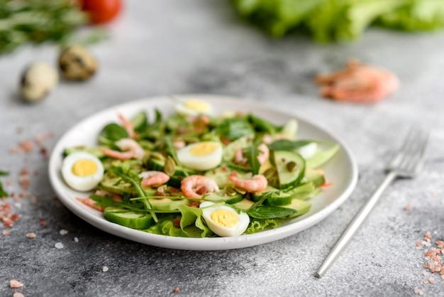 Salade met garnalen, avocado, komkommer, pompoenpitten en lijnzaad met olijfolie. gezonde voedselschotel Premium Foto