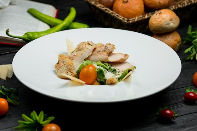 Salade met gesneden gegrilde kipfilet, salade en kerstomaatjes Gratis Foto