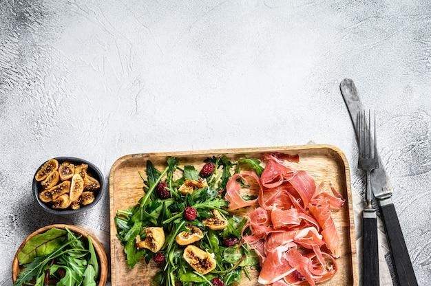 Salade met parma, prosciutto-ham, rucola en vijgen. italiaanse antipasti. Premium Foto