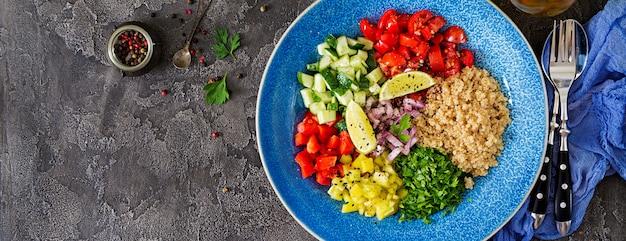 Salade met quinoa, rucola, paprika, tomaten en komkommer in kom op een donkere achtergrond. gezonde voeding, dieet, detox en vegetarisch concept. boeddha schaal. bovenaanzicht banner. plat leggen Premium Foto