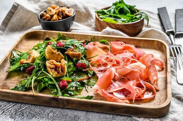 Salade met serrano jamon, ham, rucola en vijg. antipasto., bovenaanzicht. Premium Foto
