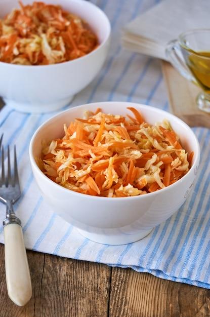 Salade met verse kool, wortelen en olijfolie in een witte kom op een houten tafel Premium Foto