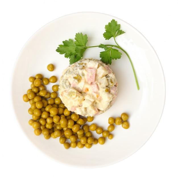 Salade olivier, groene erwten op een plaat op witte achtergrond met het knippen van weg wordt geïsoleerd die. bovenaanzicht Premium Foto