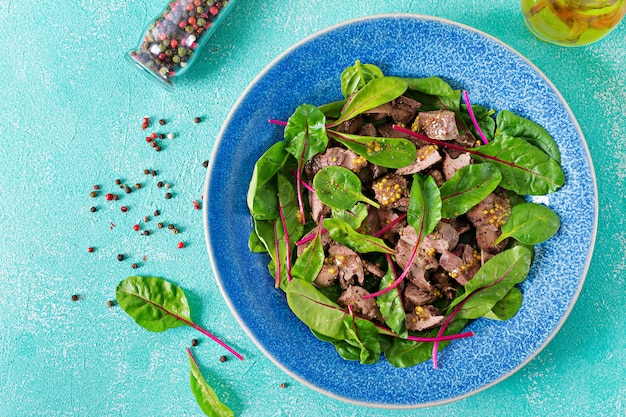 Salade van kippenlever en bladeren van spinazie en snijbiet. plat lag bovenaanzicht Gratis Foto