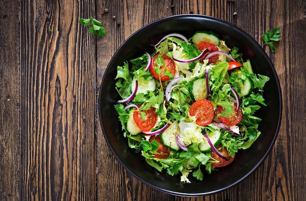 Salade van tomaten, komkommer, rode uien en slabladeren. gezond zomervitaminemenu. veganistisch plantaardig voedsel. vegetarische eettafel. bovenaanzicht plat leggen Premium Foto