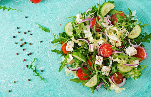 Salade van verse groenten - tomaat, komkommer en feta-kaas in griekse stijl. plat leggen. bovenaanzicht Gratis Foto
