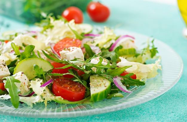 Salade van verse groenten - tomaat, komkommer en feta-kaas in griekse stijl Gratis Foto