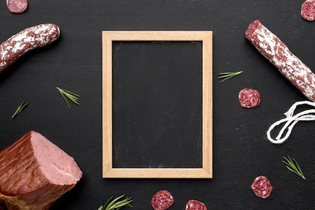 Salami en filetvlees met frame op bureau Gratis Foto