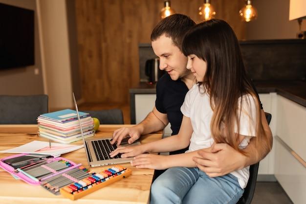 Samenhorigheid in het gezin, online leren. de vader en de dochter die laptop met behulp van doen thuiswerk Premium Foto
