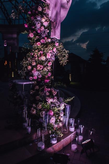 Samenstelling buitenshuis gemaakt van rozen en groen met kaarsen verlicht in de nacht Gratis Foto