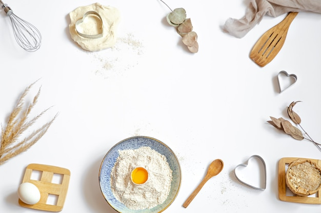 Samenstelling met bakselingrediënten en keukenaccessoires op een witte tafel. Gratis Foto