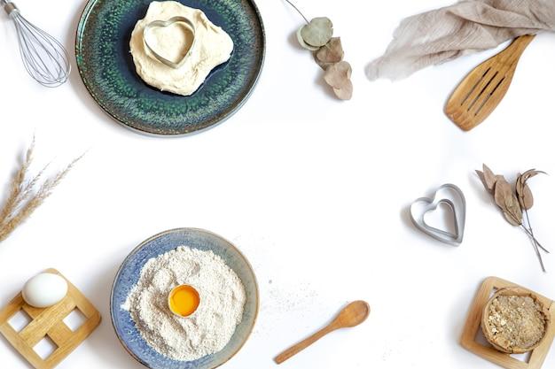 Samenstelling met bakselingrediënten en keukenaccessoires op een witte tafel. Premium Foto