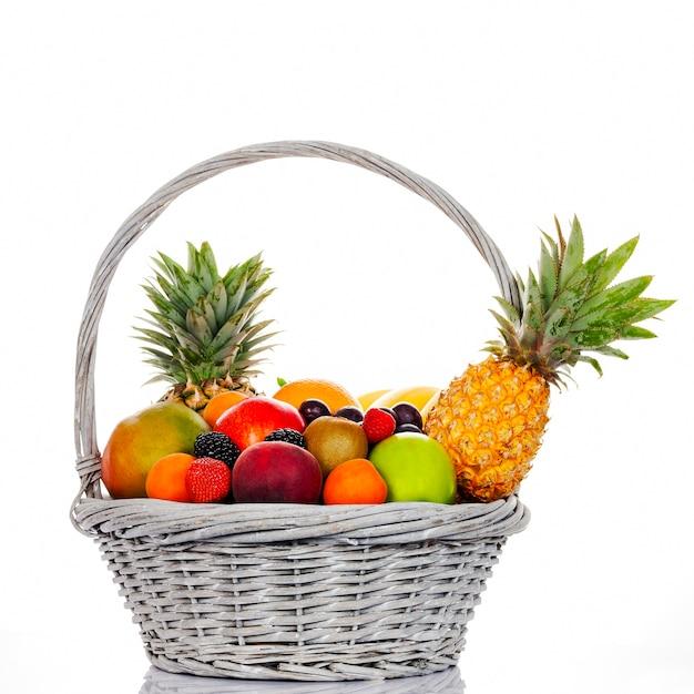 Samenstelling met diverse vruchten in rieten mand op witte achtergrond Premium Foto