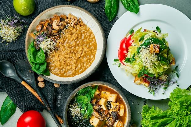 Samenstelling met een eettafel met vegetarische gerechten: risotto met champignons, frisse salade en miso soep op een grijze doek. gezond en uitgebalanceerd eten. menufoto, bovenaanzicht Premium Foto