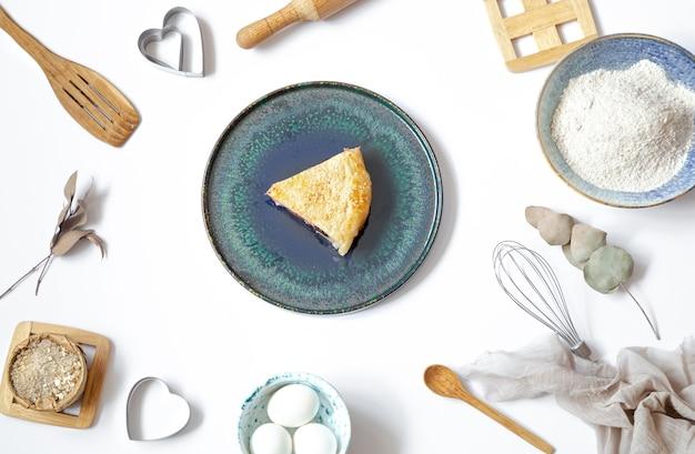 Samenstelling met een stuk taart op een bord en ingrediënten voor het koken en keukenaccessoires op witte tafel. Premium Foto