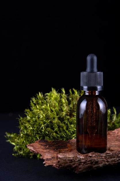 Samenstelling met glazen fles op sokkel van boomschors met echt mos Premium Foto
