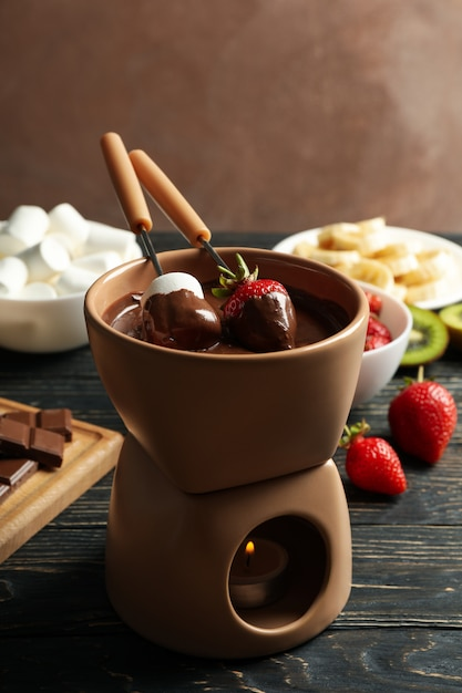 Samenstelling met ingrediënten voor chocoladefondue op houten achtergrond. fondue koken Premium Foto