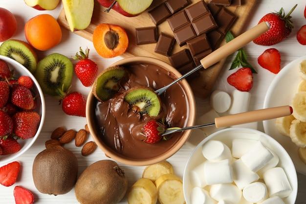 Samenstelling met ingrediënten voor chocoladefondue op witte houten achtergrond. fondue koken Premium Foto