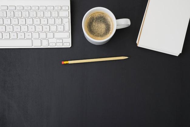 Samenstelling met koffie, potlood, notitieboekje en toetsenbord Gratis Foto