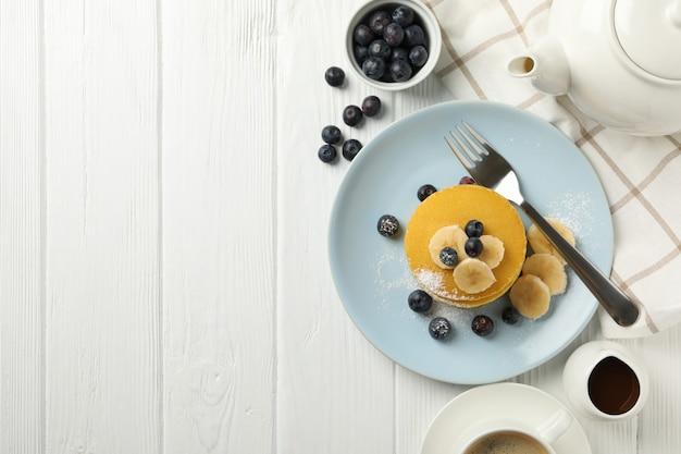 Samenstelling met pannenkoeken, bananen en bosbessen op houten ruimte. zoet ontbijt Premium Foto