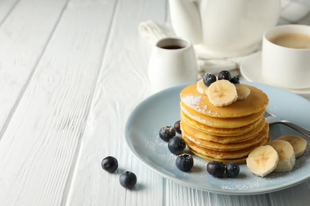 Samenstelling met pannenkoeken, bananen en bosbessen op houten tafel. zoet ontbijt Premium Foto